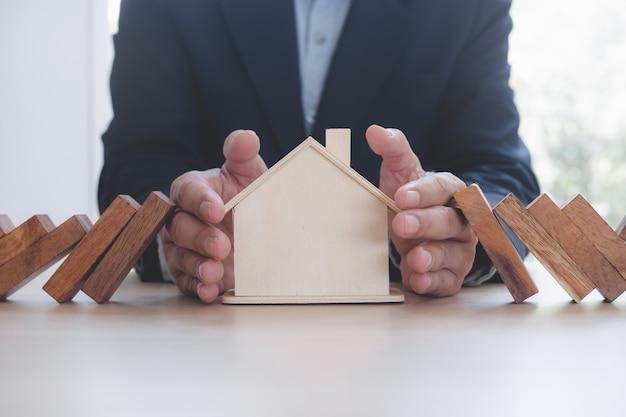 Руки останавливают эффект домино, прежде чем разрушить дом Premium Фотографии