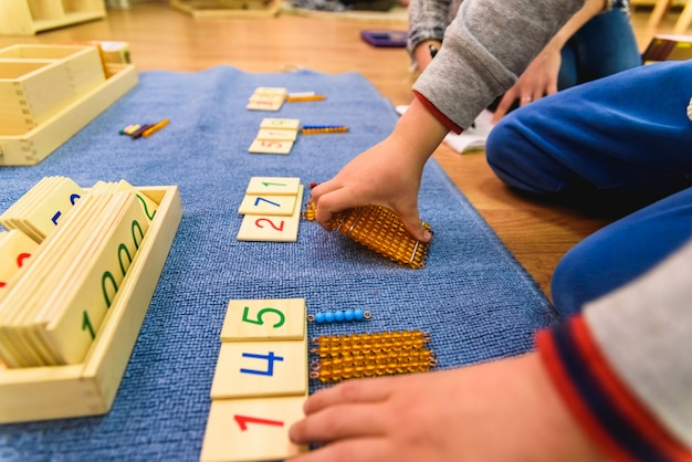 Hands of a student boy using wooden material in a montessori school. Premium Photo
