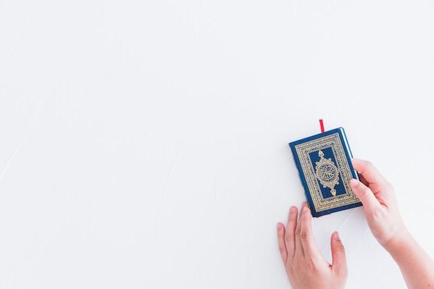 Hands taking koran book Free Photo