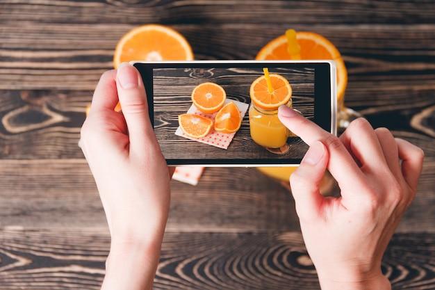 Hands taking photo of oranges. technology concept Premium Photo
