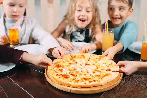Hands taking pizza slices from wooden table, close up view. Premium Photo