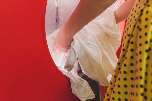 Руки для загрузки белья в стиральную машину в химчистке. Premium Фотографии