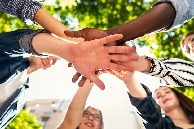 Hands tower of caucasian and afro american friends together outdoors on the hot sunny spring day Free Photo