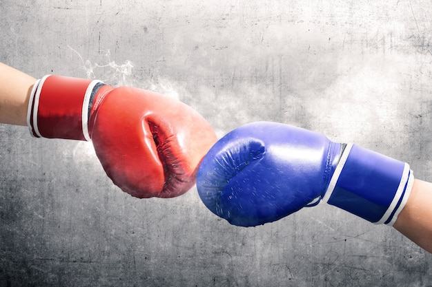 Hands of two men with blue and red boxing gloves bumped their fists Premium Photo