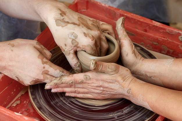 Hands of two people create pot, potter's wheel. teaching pottery Premium Photo