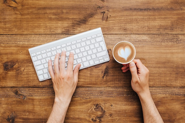 Hands typing on keyboard and holding coffee Free Photo