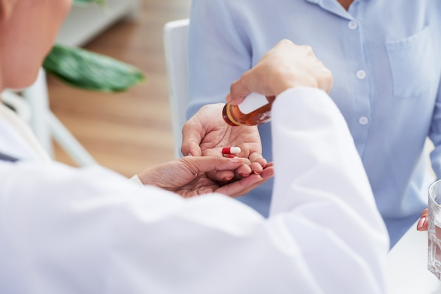 Hands of unrecognizable female doctor giving pills to patient Free Photo