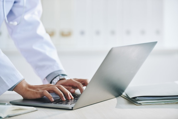 Hands of unrecognizable female doctor using laptop in office Free Photo