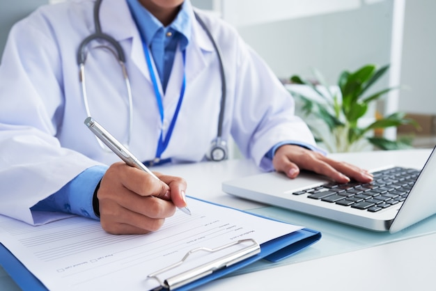 Hands of unrecognizable female doctor writing on form and typing on laptop keyboard Free Photo