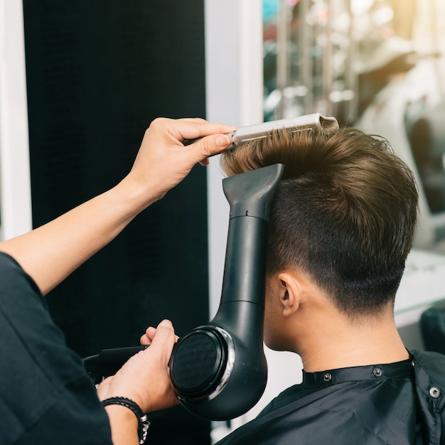 Hands of unrecognizable hairdresser giving male customer blowdry with hairdryer and comb Free Photo