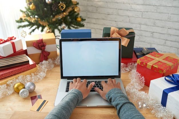 Hands of unrecognizable man buying presents online Free Photo