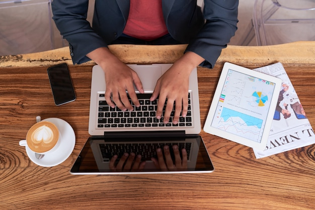 Hands of unrecognizable man sitting at wooden table in cafe and working on laptop Free Photo