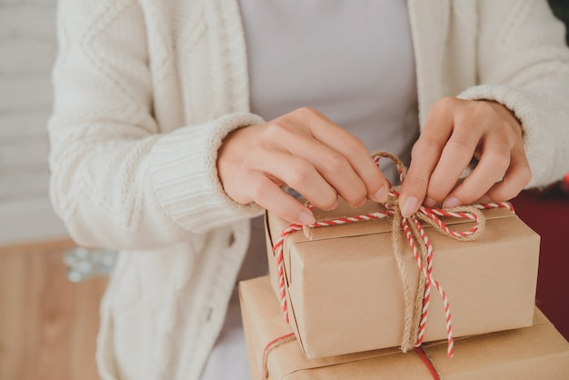Hands of unrecognizable woman tying up christmas presents with decorative twine Free Photo