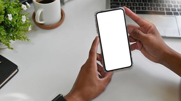 Руки, используя макет смартфона на офисном столе. Premium Фотографии