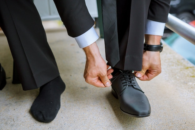 Hands of wedding groom getting ready in suit putting his wedding shoes. Premium Photo