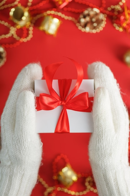 Hands in white knitted mittens holding a gift on a red background. white box with red ribbon. sustainable holiday lifestyle. christmas decorations Premium Photo