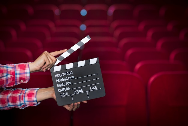 Hands with clapperboard in cinema Free Photo