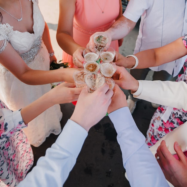 Hands with glasses of champagne friends at the wedding Premium Photo