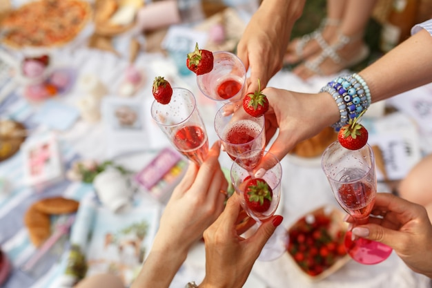 Hands with glasses cheers on summer day picnic Premium Photo