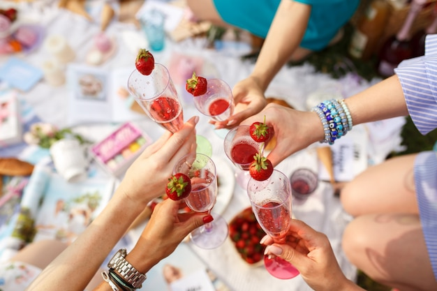 Hands with glasses cheers on summer day picnic. Premium Photo
