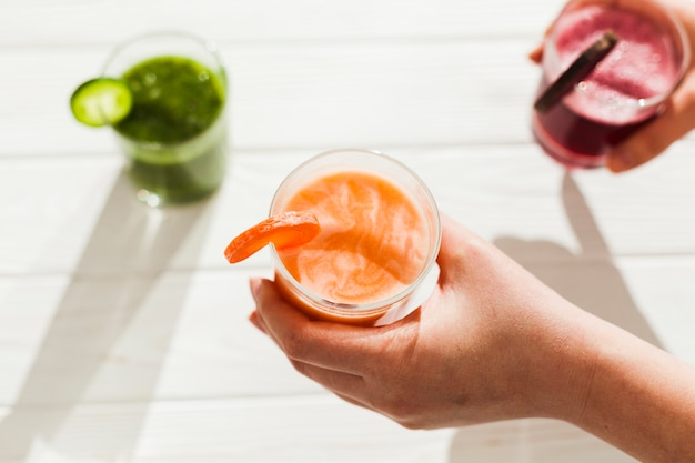 Hands with glasses of colorful drink Free Photo