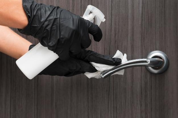 Mani con guanti che disinfettano la maniglia della porta Foto Gratuite