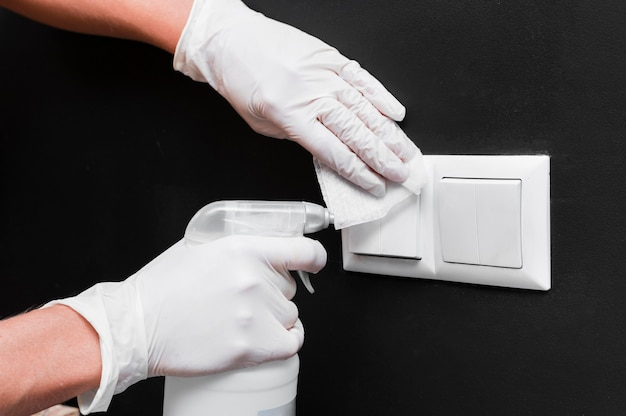Hands with gloves disinfecting light switches Free Photo