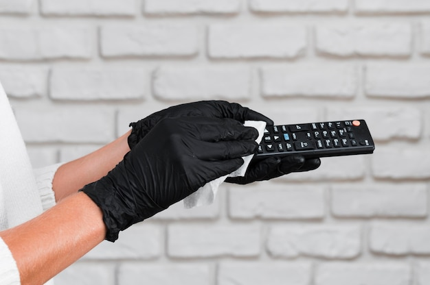 Hands with gloves disinfecting remote control Free Photo