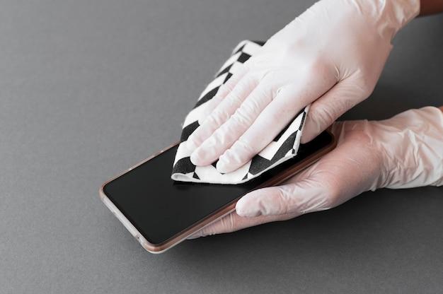 スマートフォンを消毒する手袋をした手 無料写真