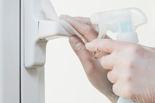 Hands with gloves disinfecting window handle Free Photo