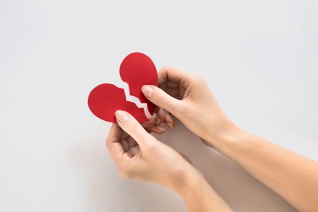 Hands with paper heart broken Premium Photo