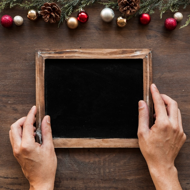 Hands with photo frame near christmas decorations Free Photo