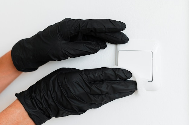 Hands with surgical gloves disinfecting light switch Premium Photo