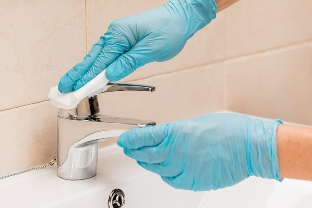 Hands with surgical gloves disinfecting sink Free Photo