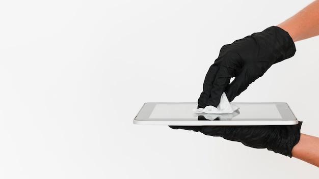 コピースペースでタブレットを消毒する手術用手袋をした手 Premium写真
