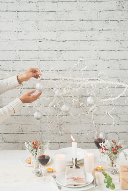 Hands of woman decorating tree branch with baubles next to tastefully arranged christmas table Free Photo