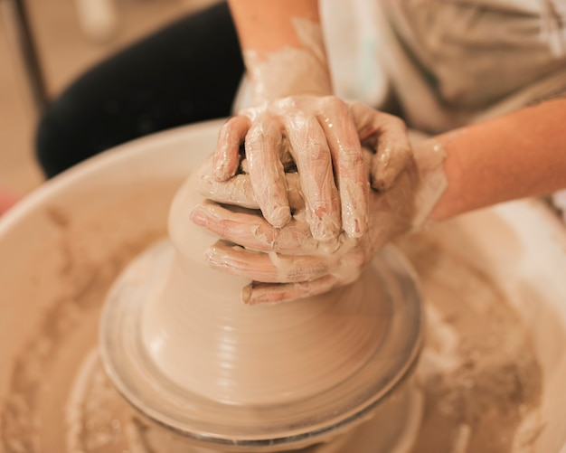 Hands of woman in process of making clay bowl on pottery wheel Free Photo