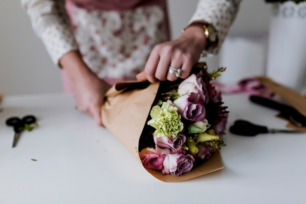 Hands of woman wrapping bunch to paper Premium Photo