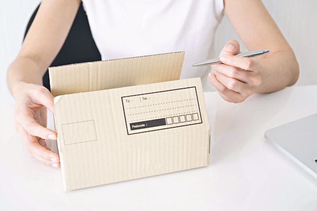 Hands of woman writing on cardboard box at table, working at home concept Premium Photo