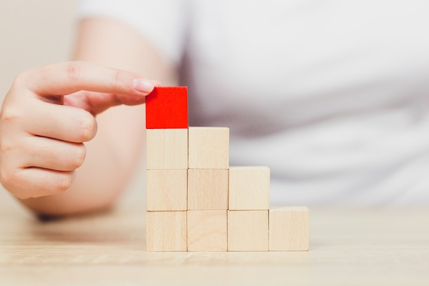 Hands of women,stacking wooden blocks into steps. Premium Photo