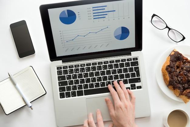 Руки, работающие на ноутбуке с диаграммой на нем Бесплатные Фотографии