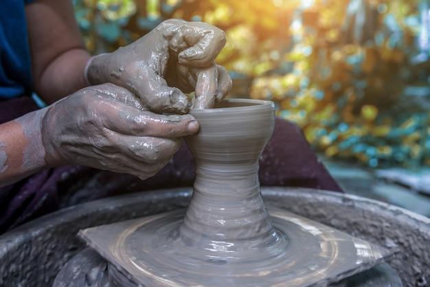 Hands working on pottery wheel Premium Photo
