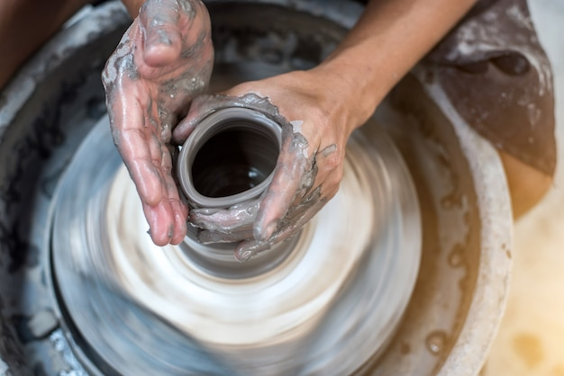 Hands working on pottery wheel Premium Photo