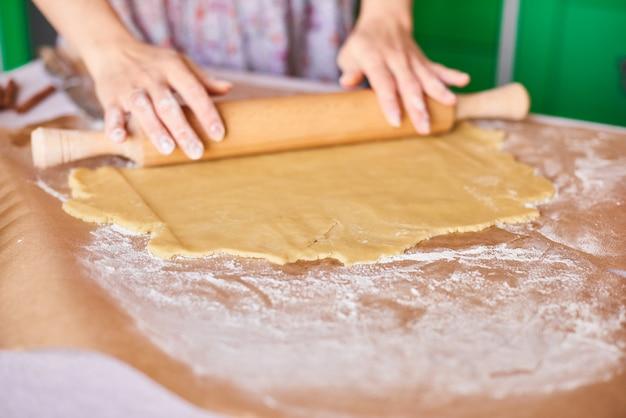 Руки работают с тестом приготовления рецепта хлеба. женские руки, делая тесто для пиццы. женские руки раскатывают тесто. мама раскатывает тесто на кухонной доске скалкой Premium Фотографии