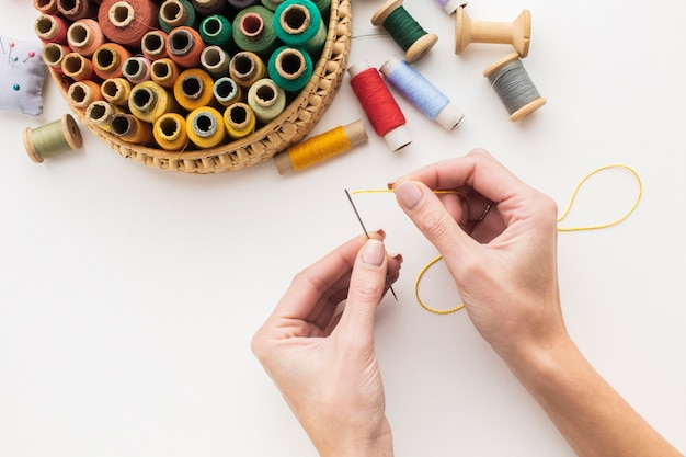 Hands working with needle and sewing thread Free Photo