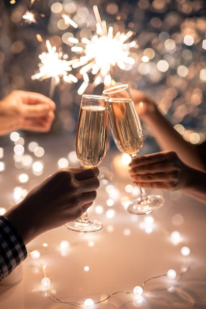 Hands of young couple clinking with flutes of champagne on space of two humans holding sparkling bengal lights Premium Photo