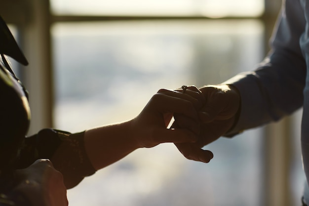 Hands of a young couple with a ring. close up of man giving diamond ring to woman Premium Photo