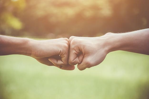 Hands of young man people fist bump team teamwork Premium Photo