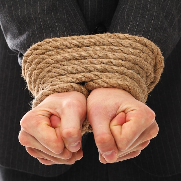 The hands of a young man tied with rope Free Photo