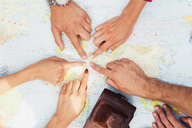 Hands of young people are pointing to travel map. Premium Photo